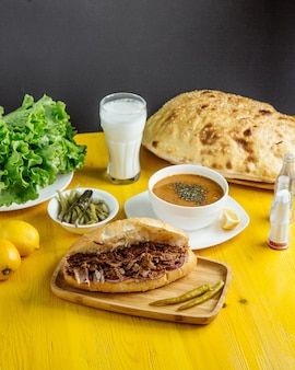 Side view of beef meat doner in bread served with pckles and soup on the table
