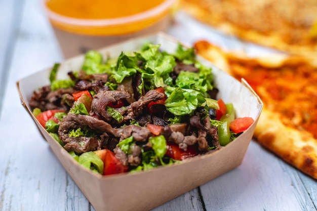 Side view beef salad sliced red meat with tomato bell pepper and lettuce in box