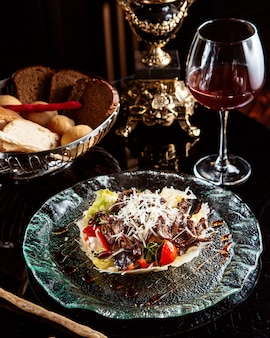 Side view of beef salad with vegetables and parmesan cheese on a plate with red wine on the table