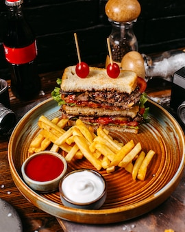 Side view of beef sandwich with tomatoes served with french fries and sauces on plate