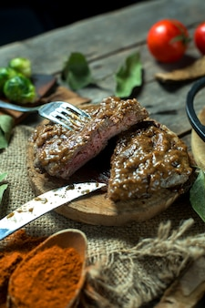 Side view of beef steak with peppercorn sauce on wooden board