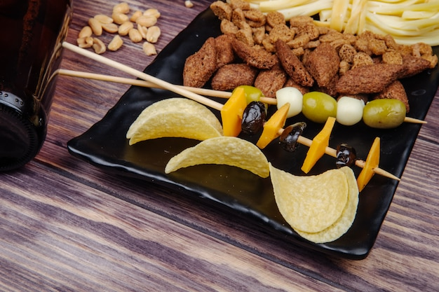 Side view of beer snacks potato chips skewers with pickled olives and cheese and bread crackers on a black tray on rustic