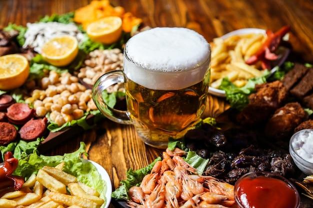 Вид сбоку на пивные закуски, колбаски, семена гороха и картофель фри с дольками лимона на подставке с бокалом пива