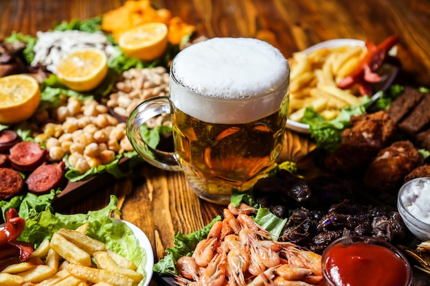 Side view beer snacks sausages peas seeds and fries with lemon wedges on a stand with a glass of beer