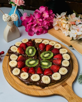Vista laterale della cialda belga ricoperta di cioccolato fondente e frutti su una tavola di legno