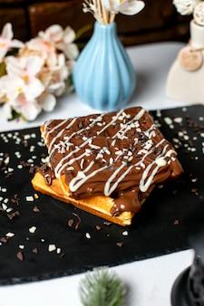 Vista laterale della cialda belga con cioccolato in cima sul tavolo