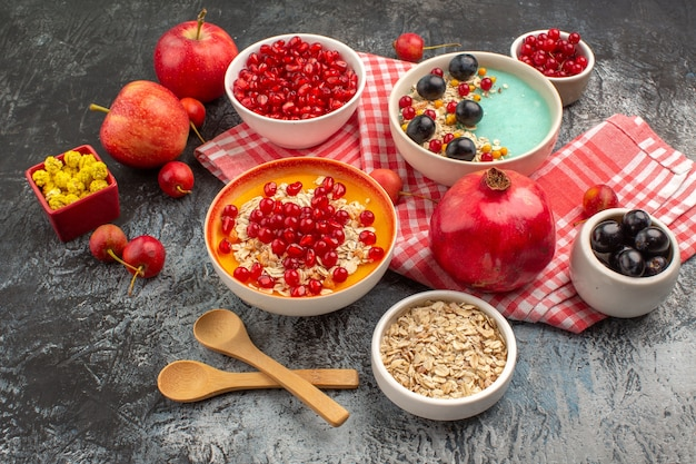 Вид сбоку ягоды семена граната виноград овсяные хлопья яблоки конфеты на скатерти ложки