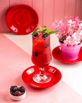 Side view of berry cocktail with chopped ice and mint in a glass on pink