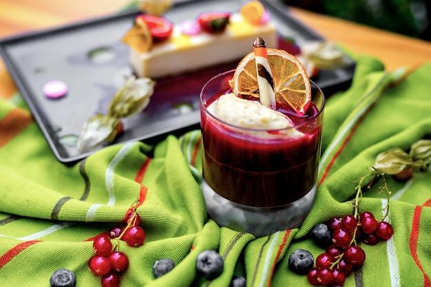 Вид сбоку ягодный суфле-десерт с кусочком сушеного апельсина и ягод