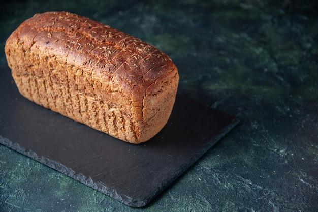 Vista laterale del pane nero su tavola nera su sfondo angosciato di colori misti