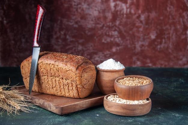 Vista laterale del pane nero fette di farina in una ciotola su tavola di legno e punte di coltello farina d'avena cruda di grano su colori misti sfondo in difficoltà