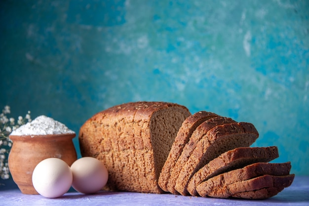 Side view of black bread slices flour eggs on light ice blue pattern background with free space
