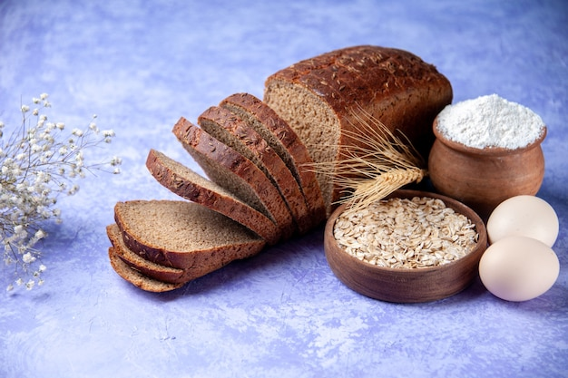 Side view of black bread slices flour oatmeal eggs on light ice blue pattern background with free space