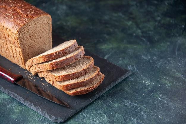 Vista laterale del coltello per fette di pane nero su tavola di colore scuro su sfondo blu in difficoltà