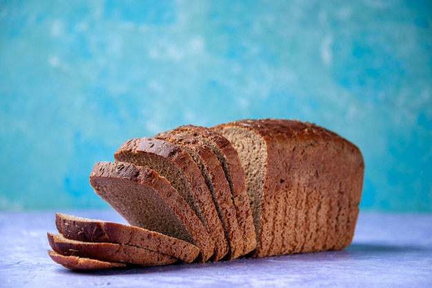 Side view of black bread slices on light ice blue pattern background with free space