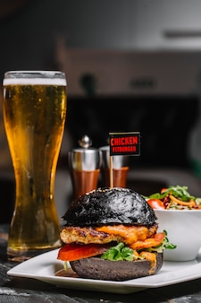 Side view of black burger with chicken cutlet melted cheese and vegetables on a plate with a glass of beer on the table