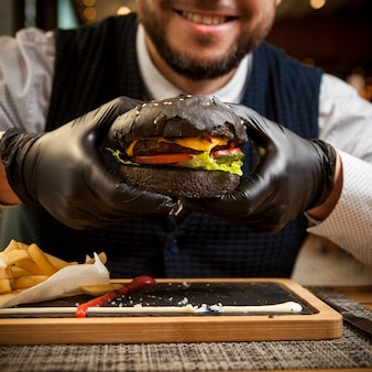 Side view black burger with disposable gloves and human hand and french fries in wooden tray on restaurant