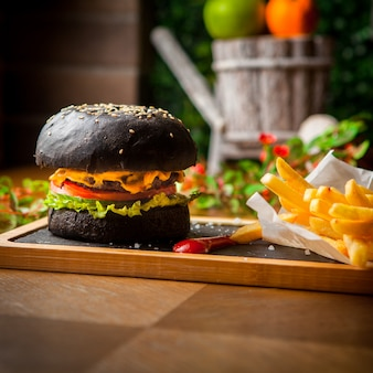 Side view black burger with french fries and ketchup in wooden tray on wooden table