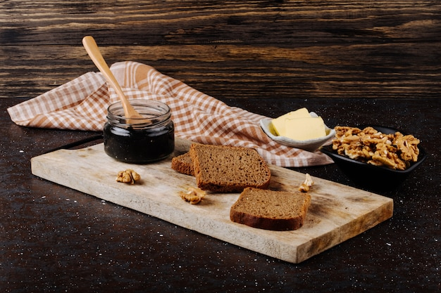 Side view black caviar jar with wooden spoon rye bread butter and walnut on a board