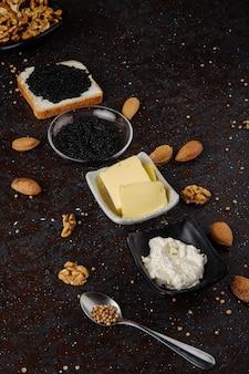 Вид сбоку чёрная икра белого хлеба с творогом чёрная икра, масло миндаля и грецкого ореха на чёрной поверхности