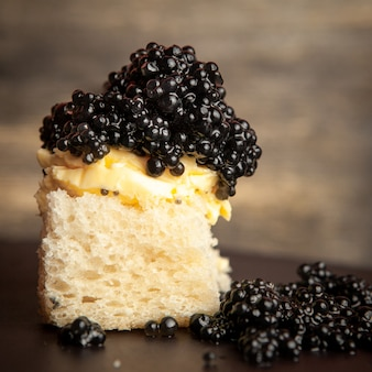 Side view black caviar with butter on bread on dark background.