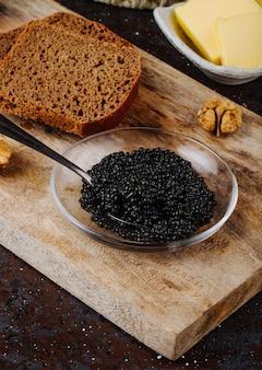 Vista laterale caviale nero con burro di pane di segale e noci su una tavola