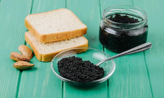 Вид сбоку черная икра с ложкой белого хлеба и миндаля на бирюзовой деревянной поверхности