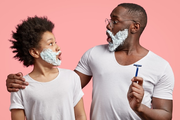 Side view of black father and son stare at each other, have shaving gel on faces, have surprised expressions