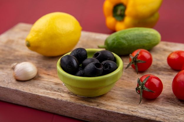 Side view of black and fresh olives in a green bowl on a wooden kitchen board with lemon tomatoes cucumber garlic on red surface