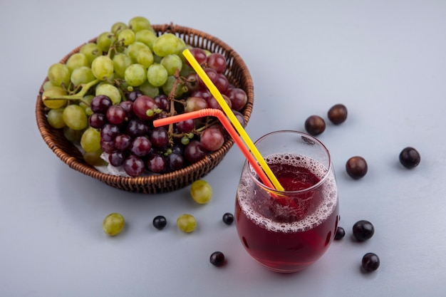 Vista laterale del succo d'uva nera e tubi per bere in vetro con uva nel cestino e su sfondo grigio