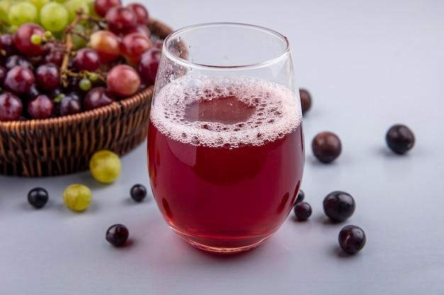 Vista laterale del succo d'uva nera in vetro e cesto di uva con acini d'uva su sfondo grigio