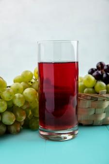Vista laterale del succo d'uva nera in vetro e uva nel cestino e sulla superficie blu e sfondo bianco