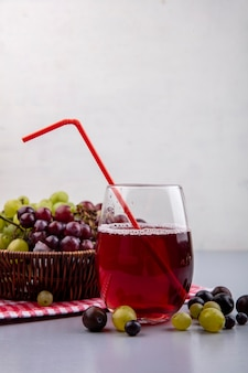Side view of black grape juice in glass with grapes in basket on plaid cloth and on gray surface and white background