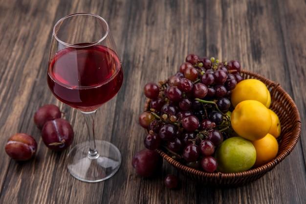 Vista laterale del succo d'uva nera nel bicchiere da vino e cesto di uva pluot e nettacots su fondo di legno