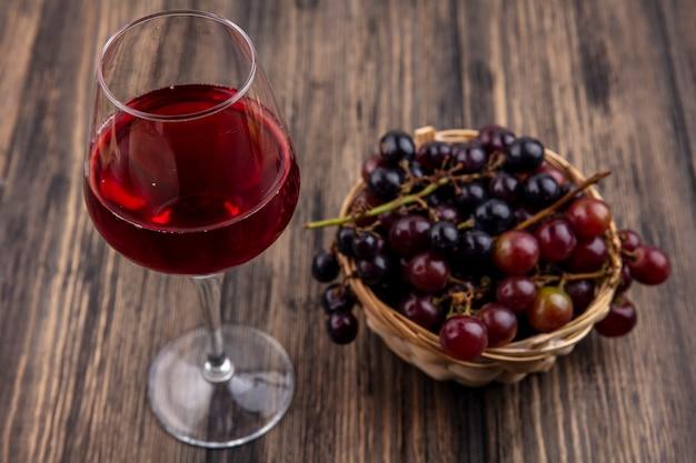 Vista laterale del succo d'uva nera nel bicchiere di vino con la merce nel cestino dell'uva su fondo di legno