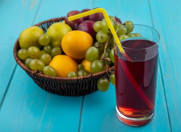 Vista laterale del succo d'uva nera con tubo per bere in vetro e cesto di uva pluots e nectacots su sfondo blu