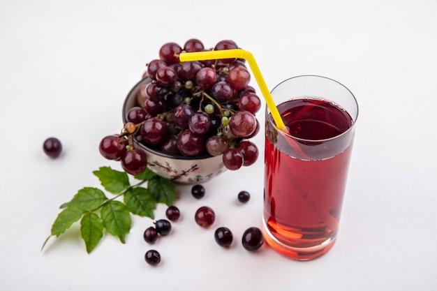 Vista laterale del succo d'uva nera con tubo per bere in vetro e ciotola di uva rossa con foglie su sfondo bianco