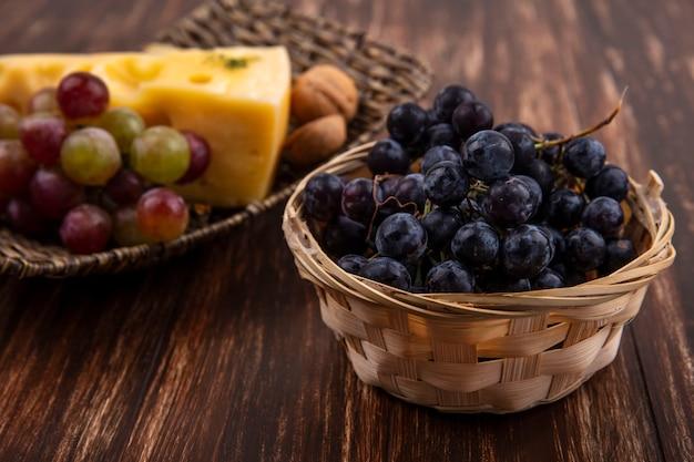 Вид сбоку черный виноград в корзине с сортами сыров и орехов на подставке на деревянном фоне