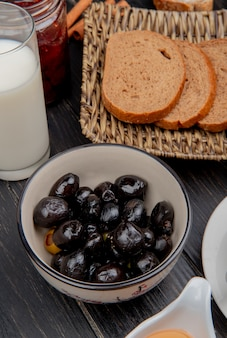 Side view of black olives in bowl with milk and sliced rye bread in basket plate on wooden surface