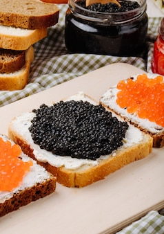 Side view black and red caviar toast rye and white bread with cottage cheese black caviar and red caviar on the table