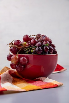 Side view of black and red grapes in bowl on plaid cloth and gray background