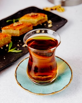 Side view of black tea in armudu glass with pakhlava