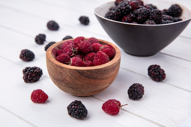 Side view of blackberry in a bowl with raspberries on a white surface