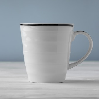 Side view of blank white cup on white table and blue background