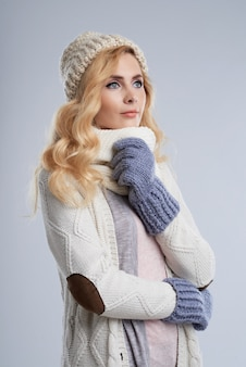 Side view of blond woman in winter clothes dreaming of wam summer