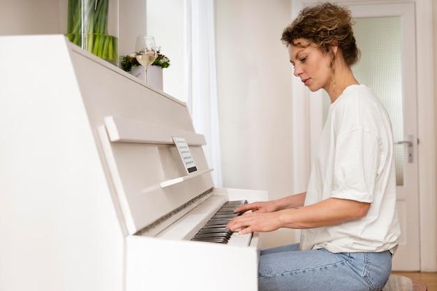 Vista laterale di una donna bionda che suona il pianoforte