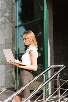 Side view of a blonde young businesswoman standing in front of office looking at laptop