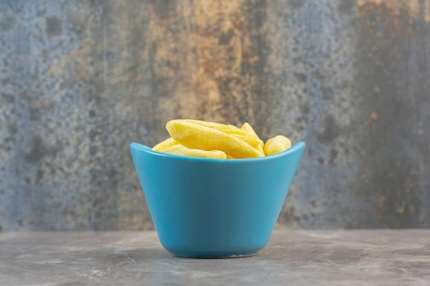 Vista laterale della ciotola in ceramica blu piena di caramelle dolci gialle.