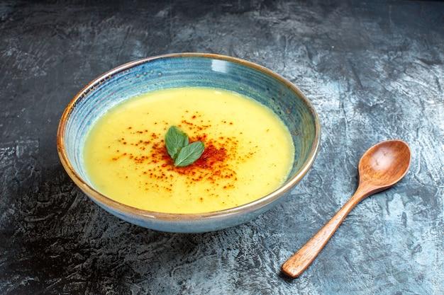 Vista laterale di una pentola blu con zuppa gustosa servita con menta e cucchiaio di legno sul tavolo blu