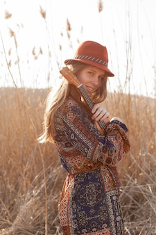 Side view of bohemian woman posing in the field with ukulele